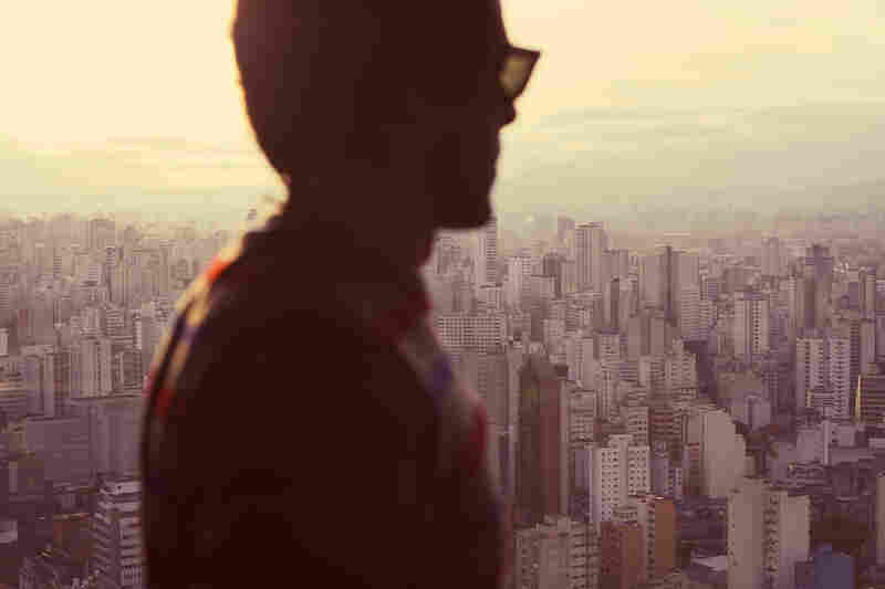 """A man in front of the countless skyscrapers of Sao Paulo. Loneliness."""