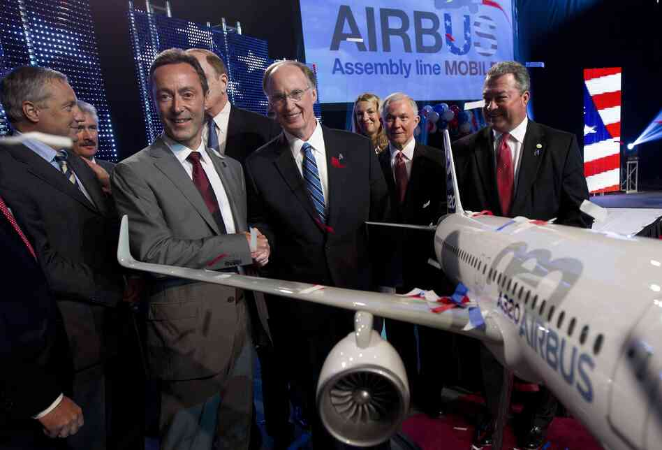 Airbus President & CEO Fabrice Bregier, second from left, shakes hands with Alabama Gov. Robert Bentley as they pose with a model of the A320 Airbus.
