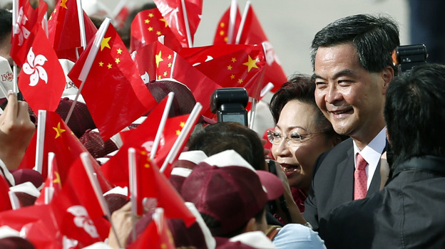 Hong Kong Chief Executive Leung Chun-ying and his wife, Regina, shake hands with supporters Sunday during a flag-raising ceremony to mark the 15th anniversary of Hong Kong's handover to China. Leung was sworn in as Hong Kong's third leader amid growing discontent with China's rule over the Asian financial center. (AP)
