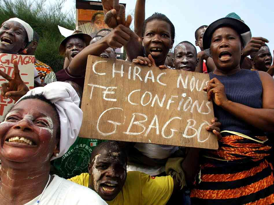 Supporters of Ivorian president Laurent Gbagbo wave upon his departure for France January 23, 2003 at Abidjan airport. Gbagbo now resides in The Hague, awaiting trial on charges of crimes against humanity during conflicts with rebels in the West African nation.