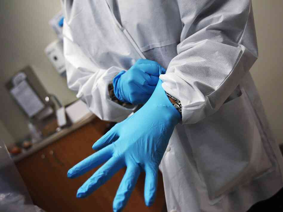 A dentist dons sterile gloves at a community health center on March 27, 2012 in Aurora, Colo. The center has received some 6,000 more Medicaid eligable patients since the passage of health care reform. Expansion of such clinics is key to serving the millions more patients set to be be covered by Medicaid under the Affordable Care Act.