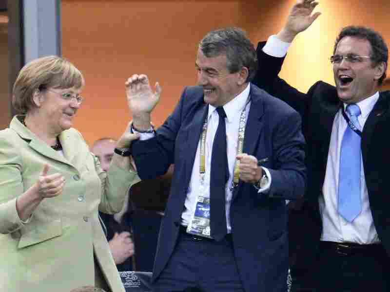 German Chancellor Angela Merkel, German football association president Wolfgang Niersbach and German Interior Minister Hans-Peter Friedrich celebrate after Philip Lahm scored against Greece during the Euro 2012