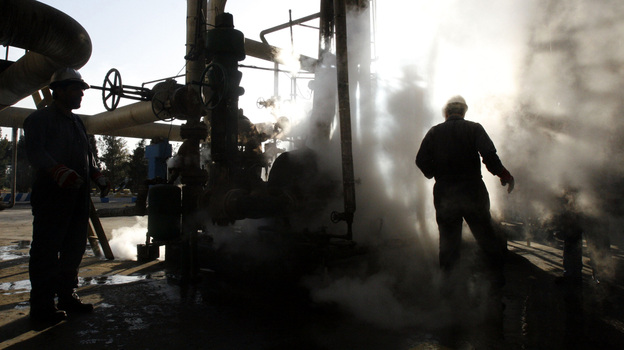 Iranian workers make repairs to a unit at Tehran's oil refinery in November 2007. It's estimated that a Western oil embargo is costing Iran about $4.5 billion each month in lost revenue. (AP)