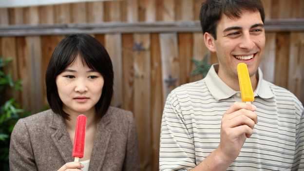NPR interns (from left) Angela Wong and Kevin Uhrmacher participate in an experiment to induce brain freeze. (NPR)