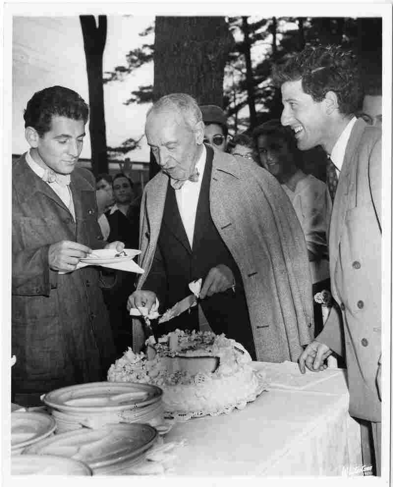 1949: Serge Koussevitsky cuts a piece of birthday cake with two young notables — Leonard Bernstein (left) and Lukas Foss (right).