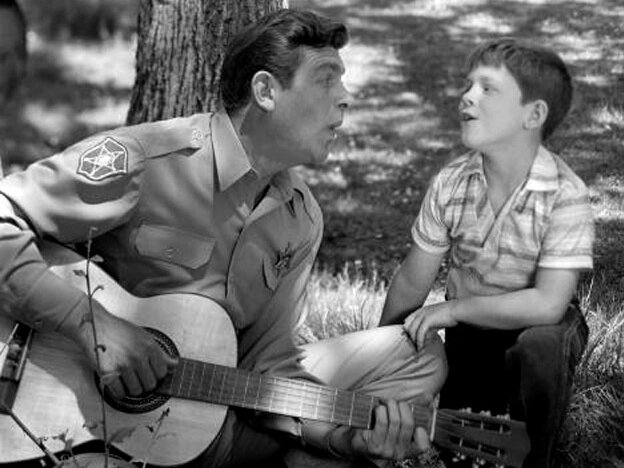"""Andy Griffith as Sheriff Andy Taylor and Ron Howard as his son, """"Opie"""" Taylor sing together in 1962."""