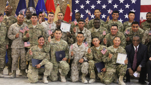 U.S. soldiers and Marines pose after being sworn in as U.S. citizens in a service at Kandahar Air Field in Afghanistan on Friday. (NPR)