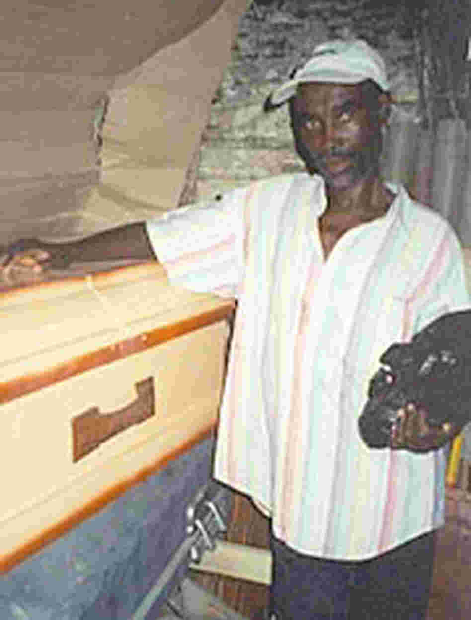St. Ker, in 2001, with the coffin he picked out for himself and a plastic bag that contains his funeral clothes. With the help of medicine, he has fought off AIDS and sold the coffin.