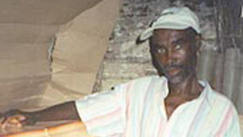 St. Ker, in 2001, with the coffin he picked out for himself and a plastic bag that contains his funeral clothes. With the help of medicine, he has fought off AIDS and sold the coffin. (NPR)