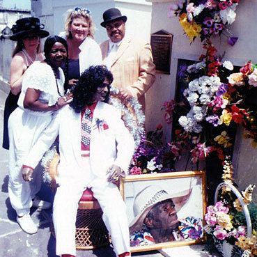 Antoinette K-Doe (second from the left) stands with friends around a statue of her deceased husband, Ernie, at the St. Louis No. 2 tomb. Antoinette is buried in the tomb, and her mother -- Ernie K-Doe's second and favorite mother-in-law, Leola Clark -- is shown in the portrait. Clark is buried in the tomb, too.