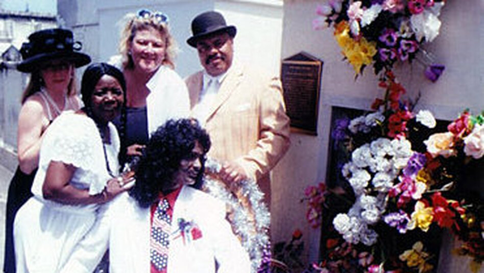 Antoinette K-Doe (second from the left) stands with friends around a statue of her deceased husband, Ernie, at the St. Louis No. 2 tomb. Antoinette is buried in the tomb, and her mother — Ernie K-Doe's second and favorite mother-in-law, Leola Clark — is shown in the portrait. Clark is buried in the tomb, too. (Courtesy of Rob Florence )