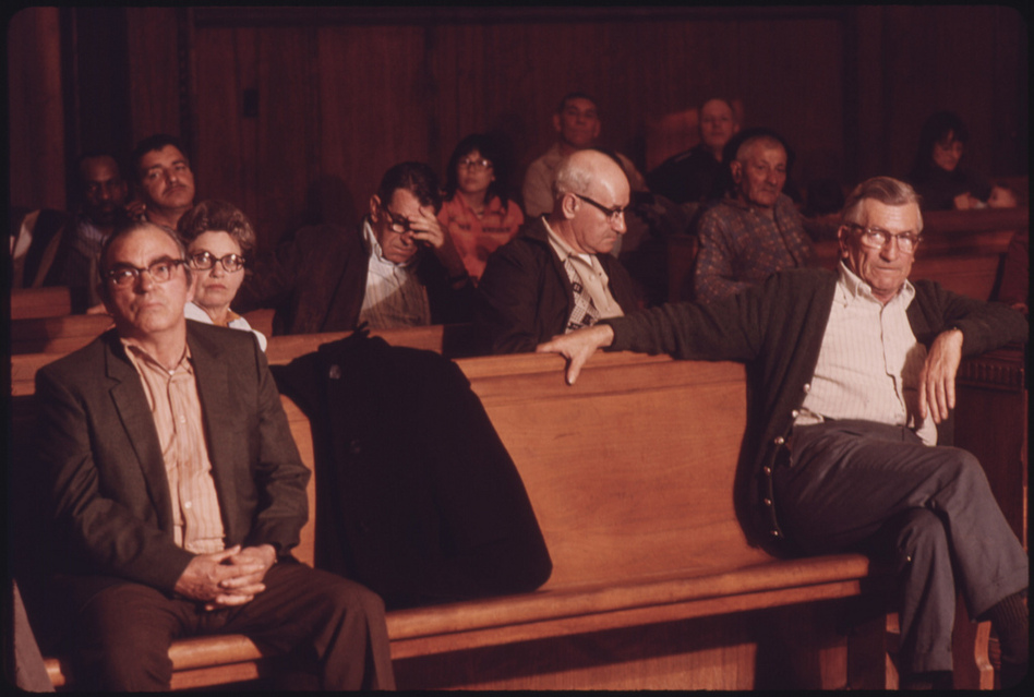 Men wait for the Beckley Black Lung Association meeting to begin. A fight for safer regulations dramatically decreased the hazards of mining. (US National Archives)