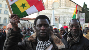 """A demonstrator holds a placard reading """"No to racism"""" in front of Santa Maria Novella church in Florence, Italy, during a Dec. 17, 2010, anti-racism march in memory of two Senegalese men who were killed four days earlier by a far-right Italian."""