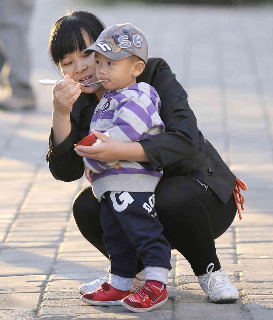 feeds her child in Beijing, Oct. 24, 2011. Experts say many Chinese ...