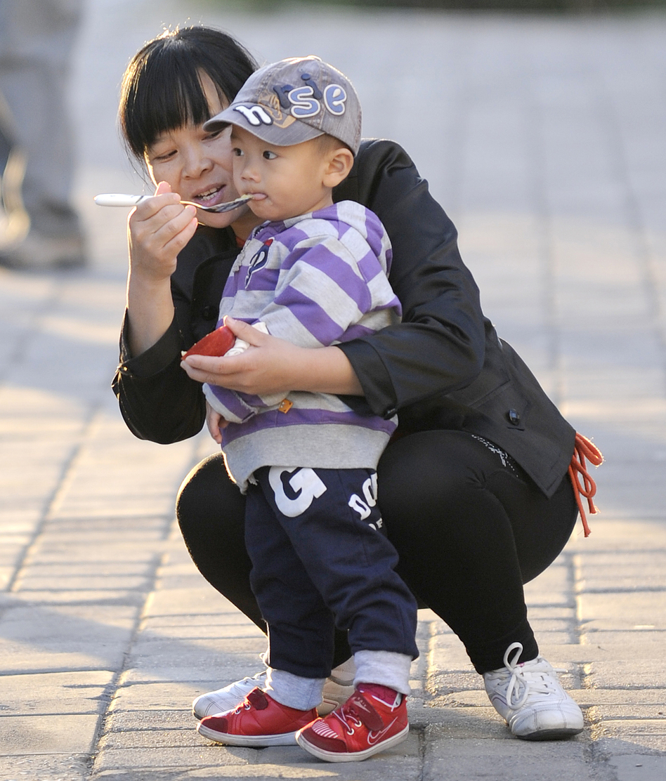 A mother feeds her child in Beijing, Oct. 24, 2011. Experts say many Chinese do not want to have additional children, regardless of official policy. (AFP/Getty Images)