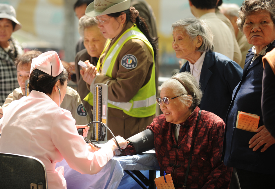 People wait to have their blood pressure checked in Shanghai in April. China's one-child policy is more than just a human rights issue; demographers warn that the low birth rate will result in a shortage of workers to drive the economy. (AFP/Getty Images)