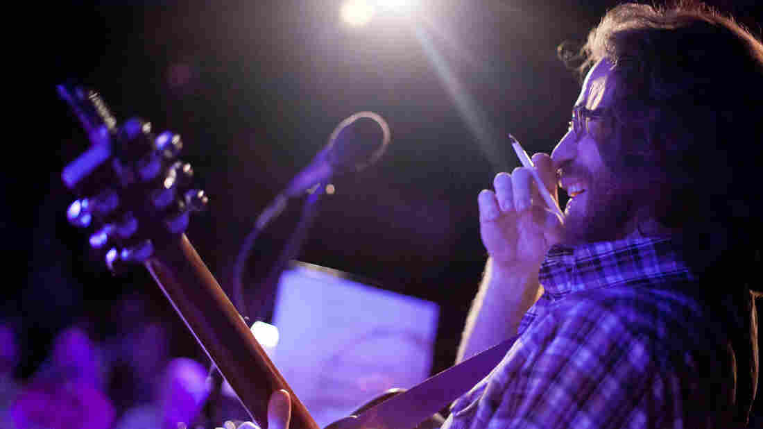Ask Me Another's resident musician, the unstoppable Mr. Jonathan Coulton, pen in hand, works his improv magic on stage.
