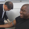 Dr. David Ho, an HIV/AIDS specialist, draws blood from Magic Johnson, one of the people featured in Endgame: AIDS in Black America.