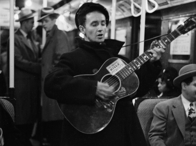 Woody Guthrie singing aboard a New York City subway train.