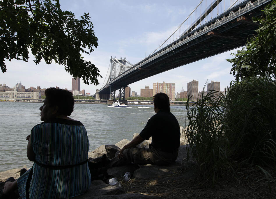 Gloria and Daniel Perez sit in a shady spot near the Brooklyn side of the Manhattan Bridge trying to beat the weather during a days-long heat wave of temperatures above 90 degrees. (AP)