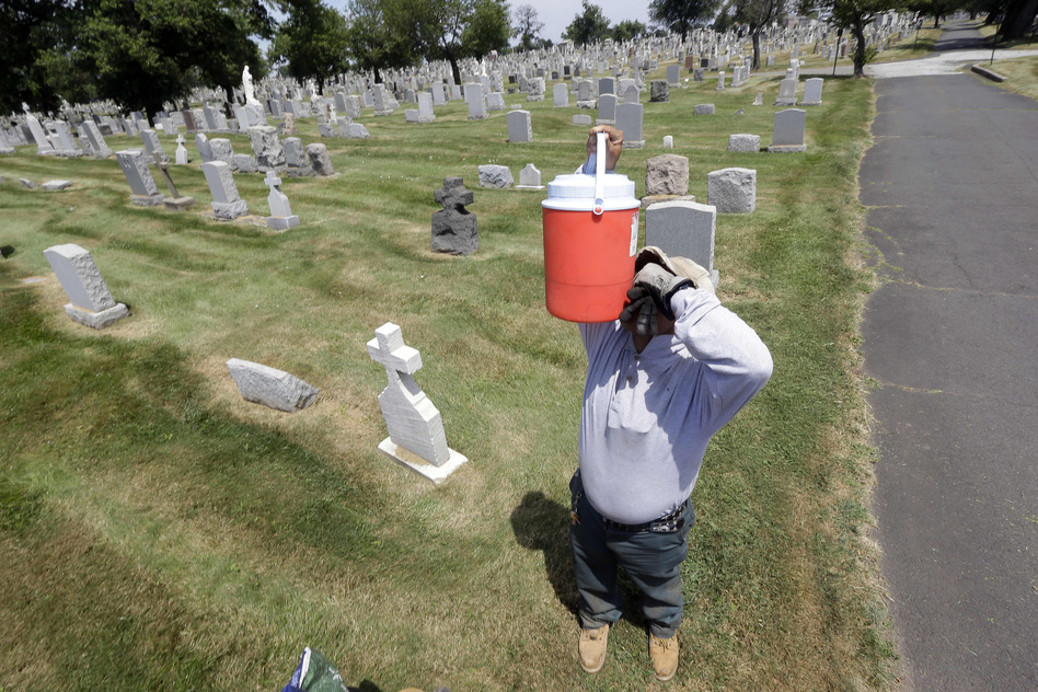 Domingo Vasquez, 36, drinks from a cooler while taking a break from mowing the lawn at Holy Sepulchre Cemetery in East Orange, N.J. Vasquez, who is originally from the Dominican Republic, said he doesn't mind the heat because he grew up with it. (AP)