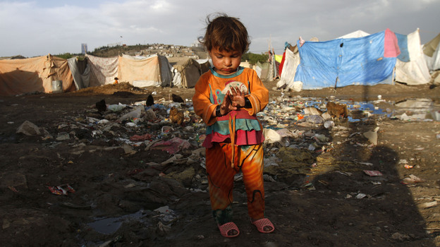 An Afghan girl stands among garbage near her home in Kabul on May 17. Some 5 million people live in Kabul, but the Afghan capital is woefully short of the infrastructure needed to support the large population.