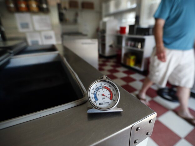 A thermometer reads the temperature atop an empty Maryland ice cream store freezer on Tuesday.  Many grocery stores and restaurants are still waiting for power to return for the first time since last weekend's severe storms.