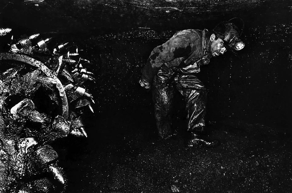 A coal miner in a classic posture walks by the bits of a continuous mining machine in Clearfield County, Pa., in 1976. (Courtesy of Earl Dotter)