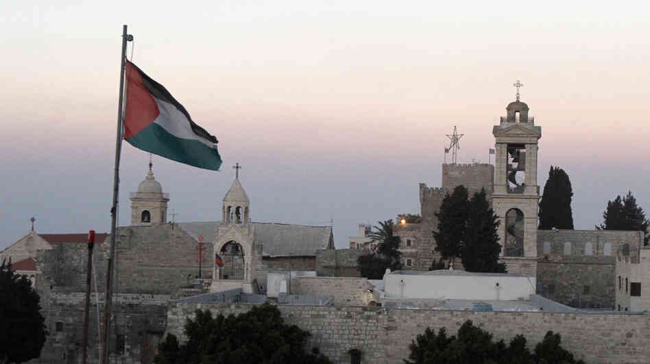 The Palestinian flag flutters in front of the Church of the Nativity in the biblical West Bank town of Bethlehem on June 29. UNESCO has given the site World Heritage status.