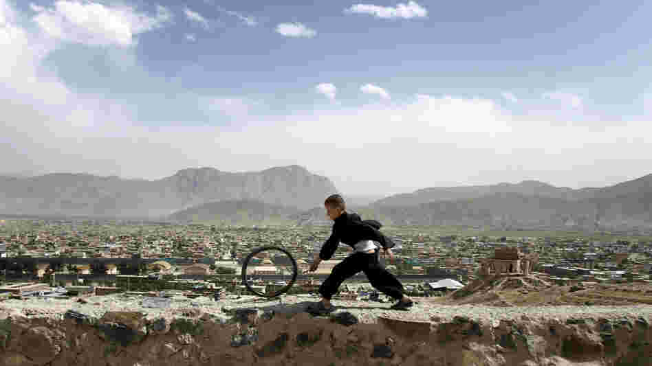 An Afghan boy pushes a wheel on the Naderkhan hill in Kabul, Afghanistan, in May. As more people have crowded to Kabul, the city center has become like a buoy floating in a sea of sprawl.