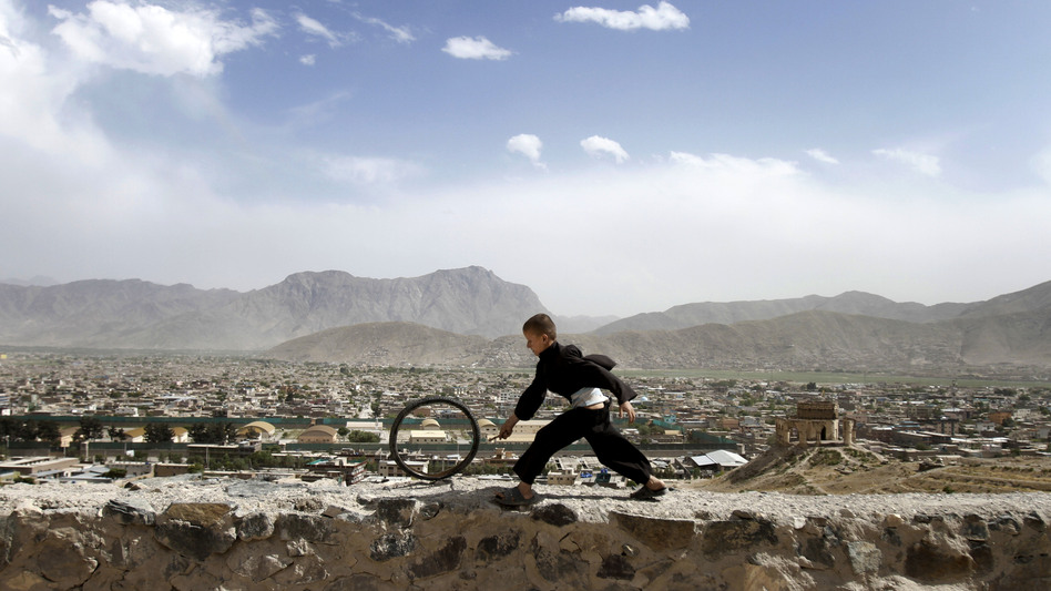 An Afghan boy pushes a wheel on the Naderkhan hill in Kabul, Afghanistan, in May. As more people have crowded to Kabul, the city center has become like a buoy floating in a sea of sprawl. (AP)
