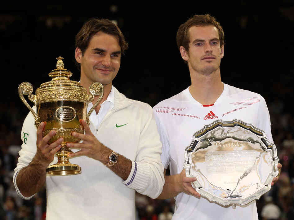 Roger Federer of Switzerland  (left) and Andy Murray of Great Britain hold up their trophies after the men's singles final match at Wimbledon Sunday.