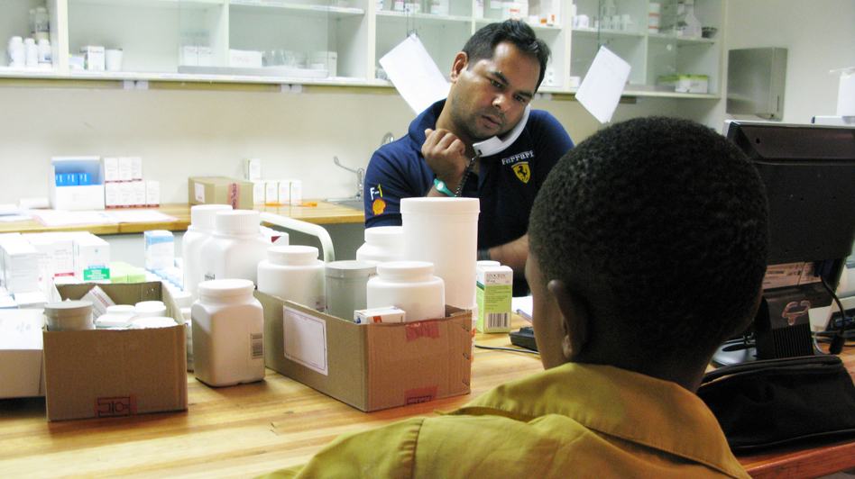 A boy waits to get his anti-AIDS drugs from pharmacist Rajesh Chandra at the Botswana-Baylor Children's Clinical Center of Excellence in Gaborone. (NPR)