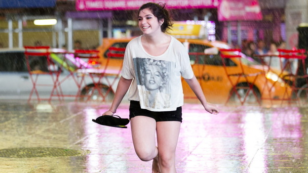 Dancing in the rain: New York City got some relief from the heat as early as Saturday, when this young woman danced in the rain in Times Square. (AP)