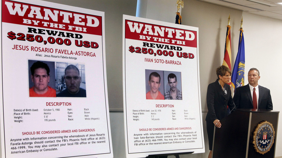With wanted posters off to the side, James L. Turgal, Jr., right, FBI Special Agent in Charge, listens as Laura E. Duffy, United States Attorney Southern District of California, announces the indictments on five suspects involved in the death of U.S. Border Patrol agent Brian Terry on Monday. (AP)