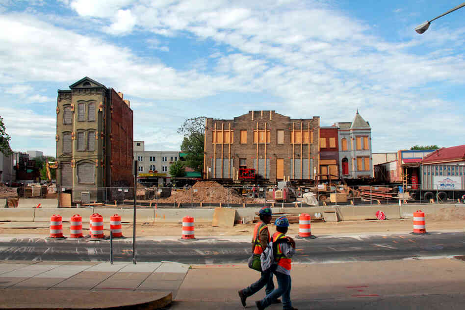Construction workers walk by the site of a major building-moving project behind NPR headquarters in Washington, D.C.