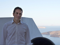 Peter Nomikos, who founded the charity Greece Debt Free about two weeks ago, sits outside the Santozeum, a family museum in Thira town, Santorini.