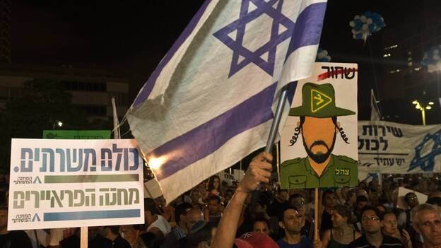 Israeli reservists soldiers and Israeli parents whose children were killed during army service attend a rally in support of a new law to mandate universal military conscription — including ultra-religious Jews who had been previously exempt and Arab Israelis, July 7, in Tel Aviv, Israel. (AFP/Getty Images)