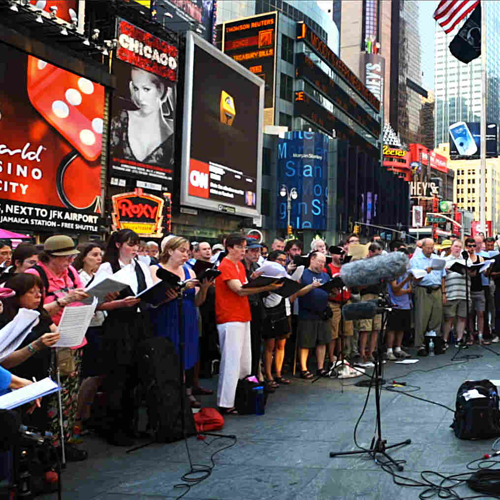 "Conductor Kent Tritle leads an impromptu choir in the world premiere of Philip Glass' ""A New Rule"" in New York's Times Square."