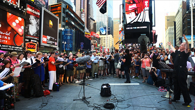 "Conductor Kent Tritle leads an impromptu choir in the world premiere of Philip Glass' ""A New Rule"" in New York's Times Square. (NPR)"