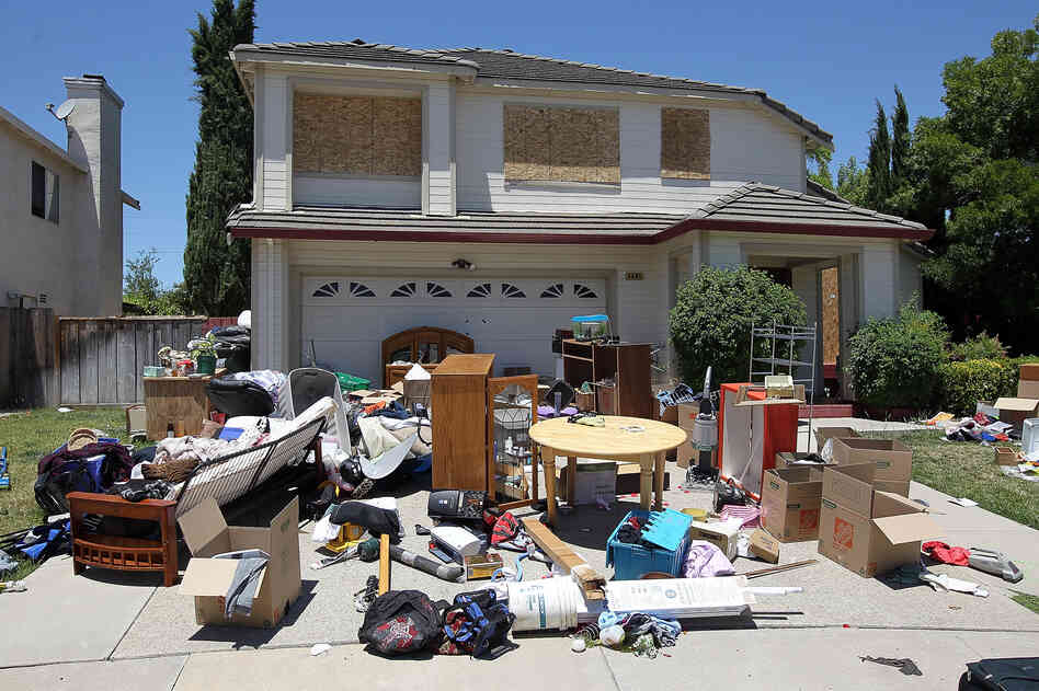 Furniture and personal belongings sit in front of a house that appears to have been foreclosed on in Antioch, California.
