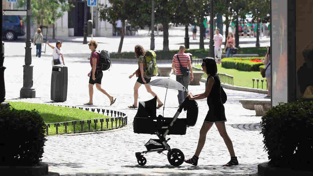 A woman pushes a pram though the Plaza de Murillo on July 3 in Madrid. Spain's custom for multiple families to live under the same roof has tied them closer together as well as their wallets. The country has the highest unemployment rate in the Eurozone, and government benefits help aid those out of work.