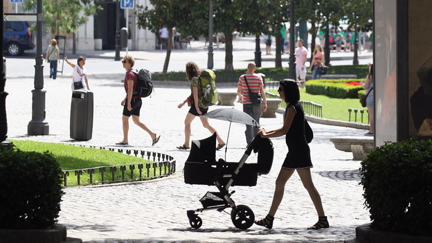 A woman pushes a pram though the Plaza de Murillo on July 3 in Madrid. Spain's custom for multiple families to live under the same roof has tied them closer together as well as their wallets. The country has the highest unemployment rate in the Eurozone, and government benefits help aid those out of work. (Getty Images)