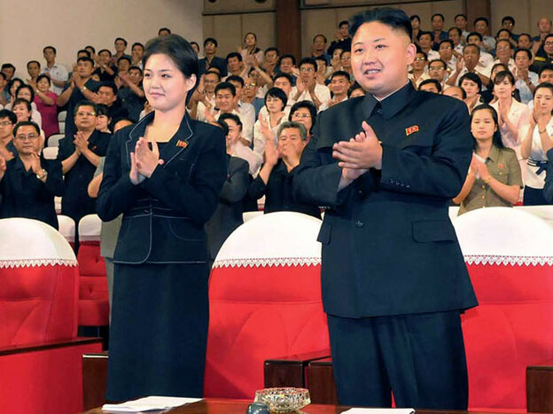 In this photo released by the Korean Central News Agency (KCNA) and distributed in Tokyo by the Korea News Service on Monday, July 9, 2012, North Korean leader Kim Jong Un, right, and a woman clap with others on Friday as they watch a performance by North Korea's new Moranbong band in Pyongyang. Observers think she is Hyon Song-wol.