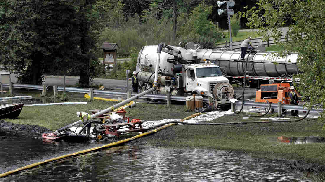 Workers in Battle Creek, Mich., use suction hoses to try to clean up an 800,000-gallon oil spill in the Kalamazoo River in July 2010.