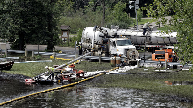 Workers in Battle Creek, Mich., use suction hoses to try to clean up an 800,000-gallon oil spill in the Kalamazoo River in July 2010. (Getty Images)