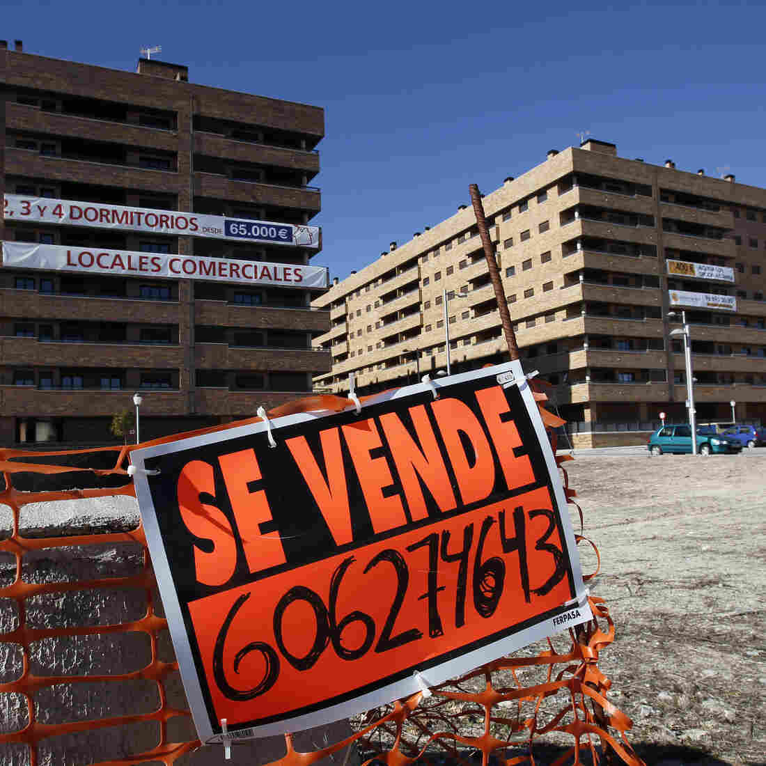 "A ""For Sale"" sign hangs outside mostly empty apartment blocks in the Madrid satellite town of Sesena in February. Banks are trying to sell billions of euros worth of property left by bankrupt developers. This is attracting bargain-hunting investors from abroad."