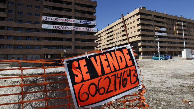 """A """"For Sale"""" sign hangs outside mostly empty apartment blocks in the Madrid satellite town of Sesena in February. Banks are trying to sell billions of euros worth of property left by bankrupt developers. This is attracting bargain-hunting investors from abroad. (Reuters/Landov)"""