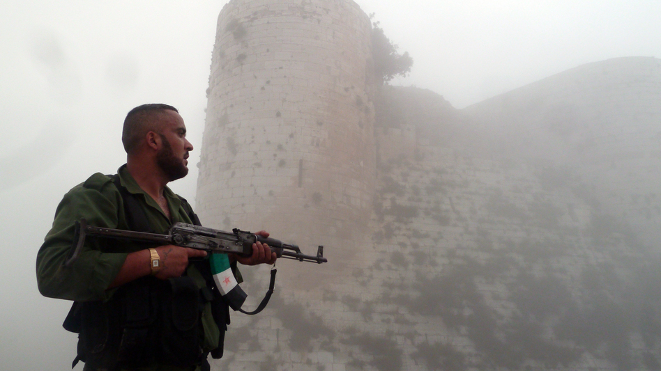 A member of the Free Syrian Army stands near a medieval castle outside Homs, a flashpoint for much of the recent fighting, last month. The Syrian army continues to wage offensives against the rebels in many places, but the rebels say they can move back and forth between northwest Syria and southern Turkey. (AFP/Getty Images)