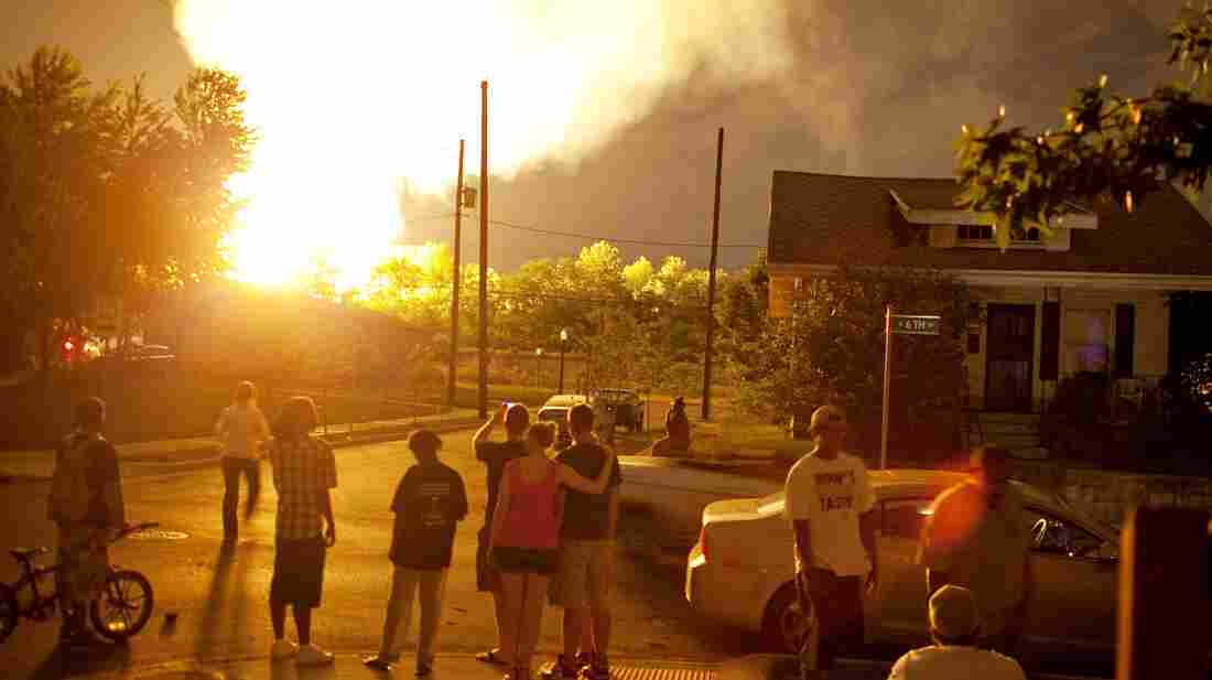 Neighbors watch a fire from a train derailment in Columbus, Ohio.